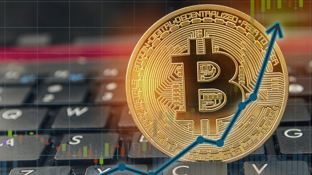 Bitcoin rising concept on laptop keyboard with up arrow chart an